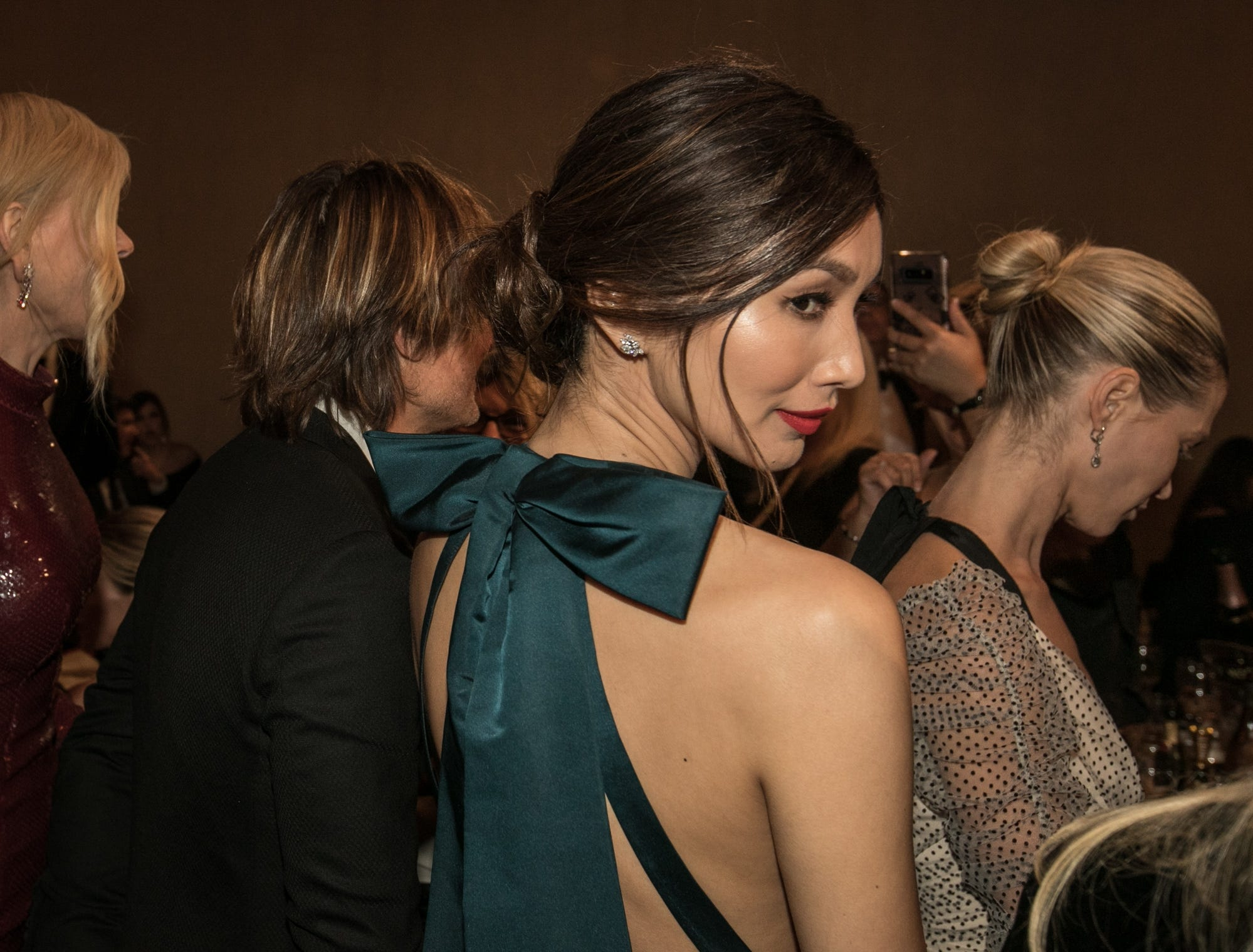 """Crazy Rich Asians"" star Gemma Chan looks over her shoulder, as Nicole Kidman and Keith Urban walk alongside."