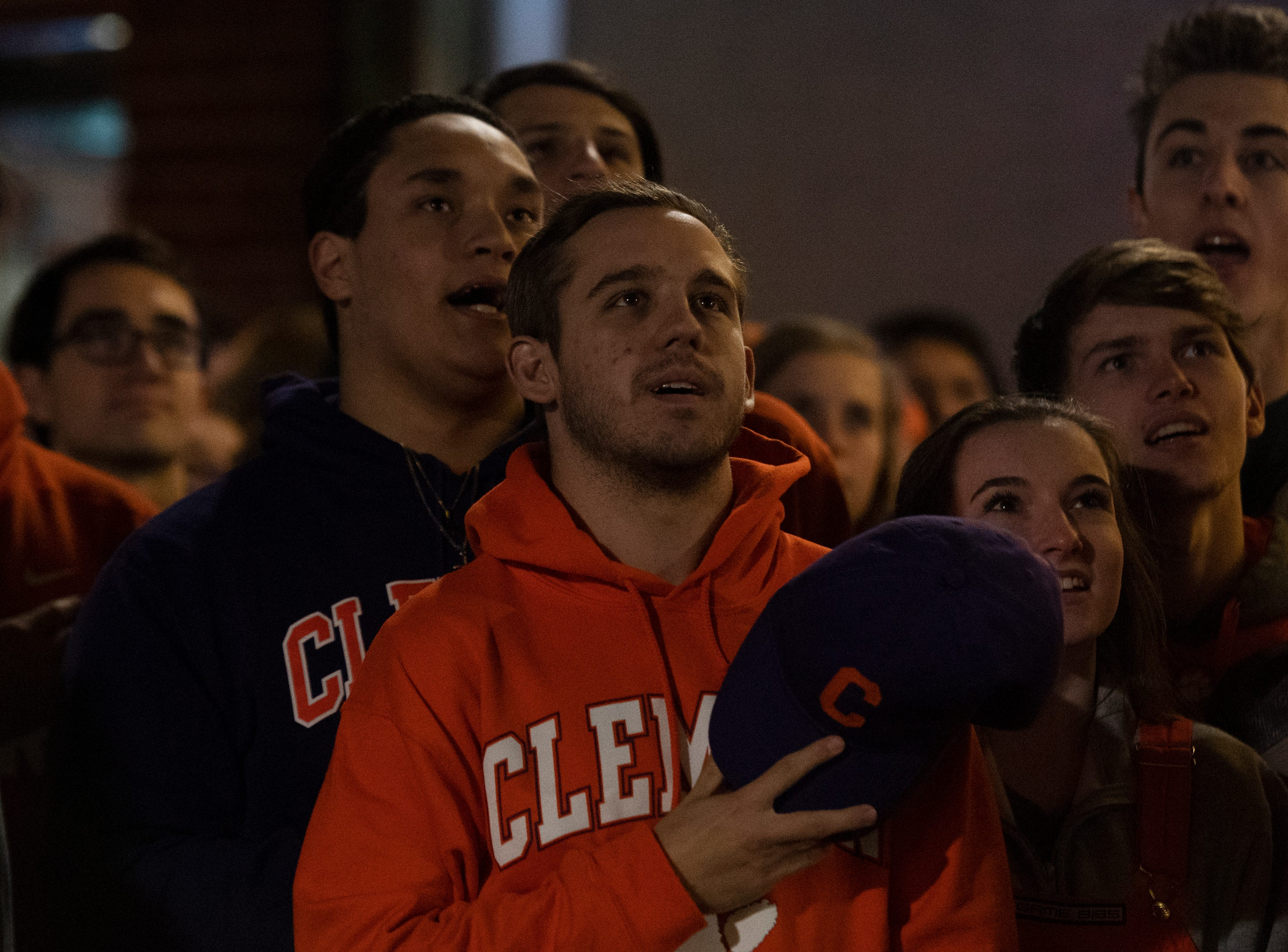 Freshman Jacob Bauman, 19, stands for the National Anthem while gathered with other Clemson fans on College Avenue to watch Clemson play Alabama in the College Football Playoff National Championship Monday, Jan. 7, 2019.
