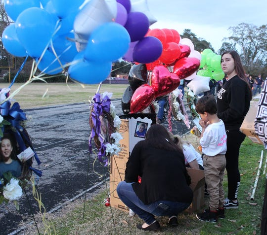 People pause to look at a poster board with photos of Cierra Bordelon and Cara Descant before a candlelight vigil Monday evening in Marksville. The girls were among five children killed last week in a Florida wreck.