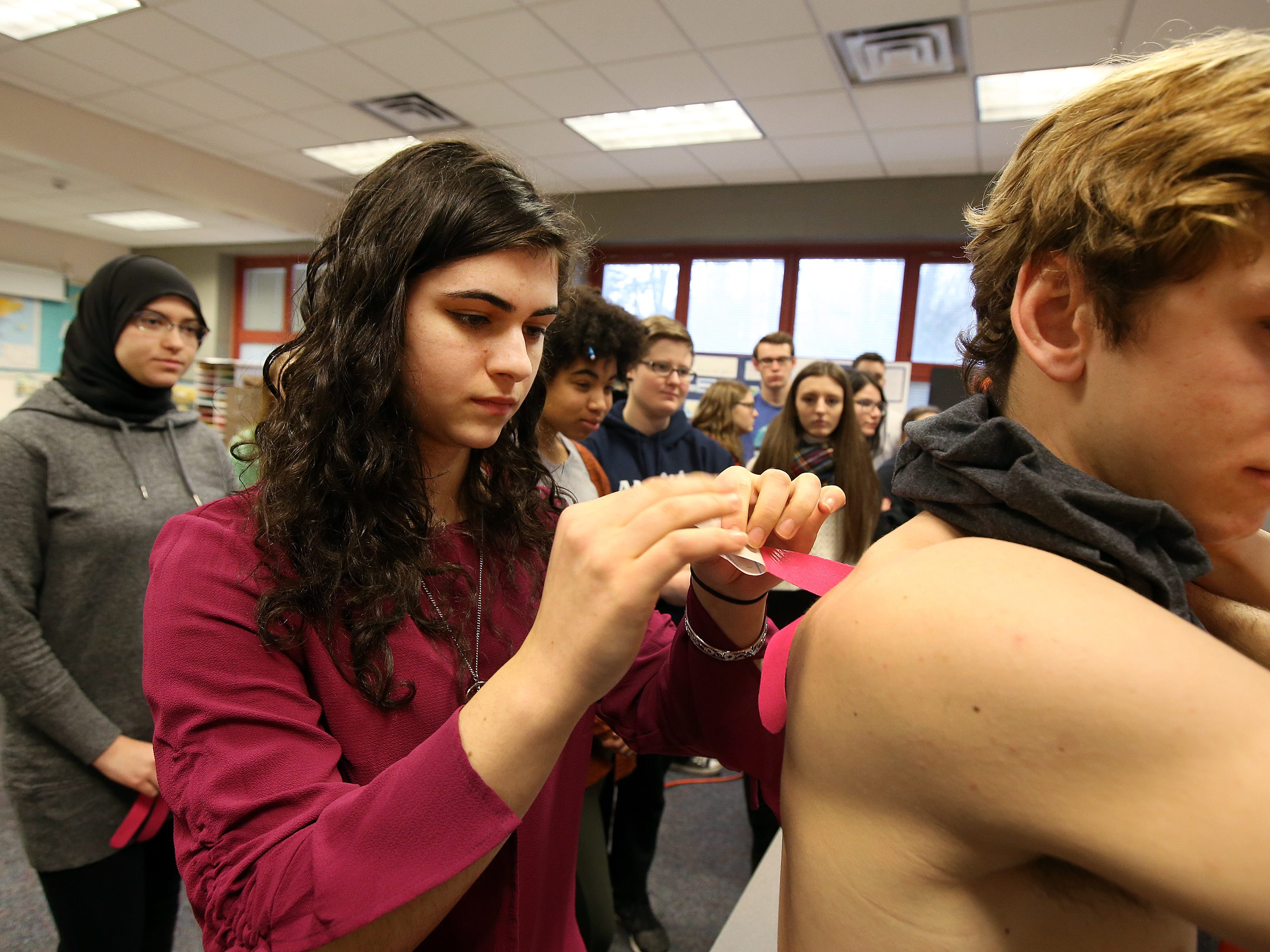 Christina Gulotta, 17, of Manalapan places kinesiology tape on the shoulder of Curran Magnusson, 18, of Spring Lake during their Intro to Physical Therapy class at Monmouth County Academy of Allied Health and Science in Neptune, NJ Tuesday January 8, 2019.
