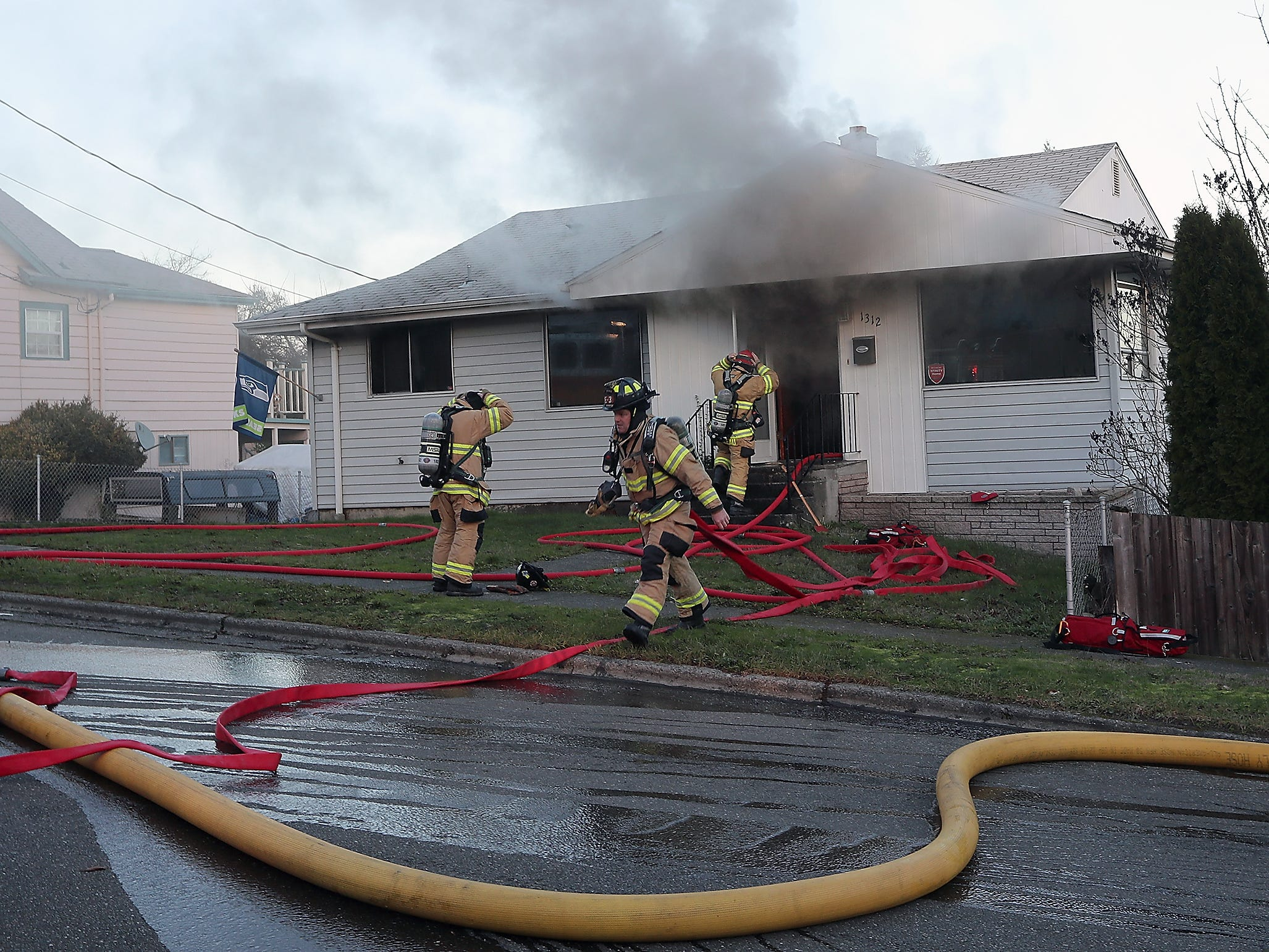 Bremerton Firefighter/Paramedic Kevin Bonsell (center) pulls hose as fellow Bremerton firefighters Capt. Brian Marceau, (right) and Doug Baier (left) don their masks before entering the home as crews extinguish a residential structure fire on Marguerite Ave. in Bremerton on Monday, January 7, 2019.
