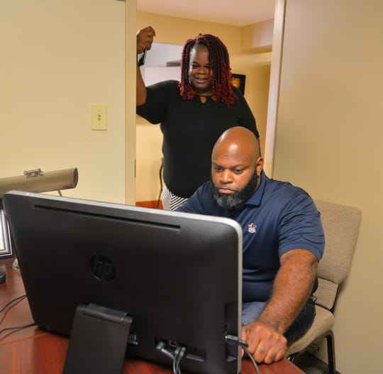. Pastor Jarvis Wash with the R.E.A.L. Church fills out his voter application online while Cecelia Thompson looks on, she just finished her application. They were at the City of Refuge Christian Center in Cocoa.