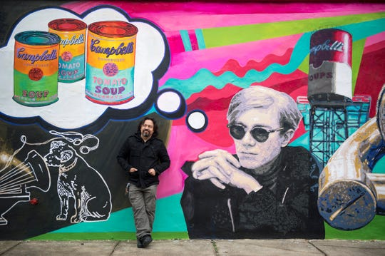 Lead artist Cesar Viveros poses with his mural at Friends Cafe Tuesday, Jan. 8, 2019 in Camden, N.J.