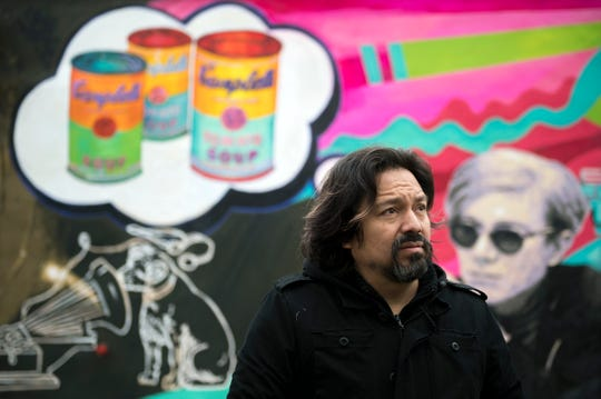 Lead artist Cesar Viveros speaks with attendees during an unveiling of his new mural at Friends Cafe Tuesday, Jan. 8, 2019 in Camden, N.J.