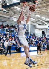 Chillicothe High School basketball's Brandon Noel hangs on the rim after dunking the ball to score for Chillicothe in a 71-40 win over Waverly. Noel committed to play basketball for Wright State University on Wednesday.