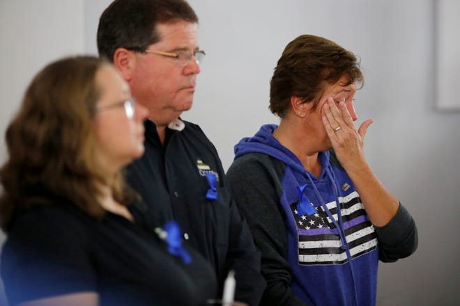 Retired police lieutenant Angela Meyer wipes tears from her eyes after giving a speech during a vigil for Colerain Police Officer Dale Woods at the community center in Colerain on Monday, Jan. 7, 2019. Woods was struck by a vehicle while responding to a separate car crash Friday night and remains in critical condition.