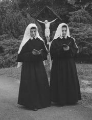 Twin sisters from Bellevue, Sr. M. Charlynn and Sr. M. Shannon,pray in front of the Wayside Cross at St. Joseph Heights in Park Hills in 1961. The twins entered the Sisters of Notre Dame in 1960.