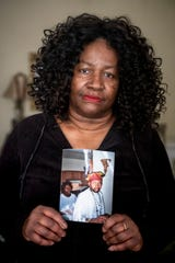 Carol Eubanks poses with a photo of her son, Mark Eubanks, Tuesday, January 8, 2019, in her West End home. Mark is in the ICU at UC Medical Center after being hit by a vehicle Friday, December 28, 2018, on Linn Street in the West End. Carol said this was the second time this year her son has been struck by a vehicle.