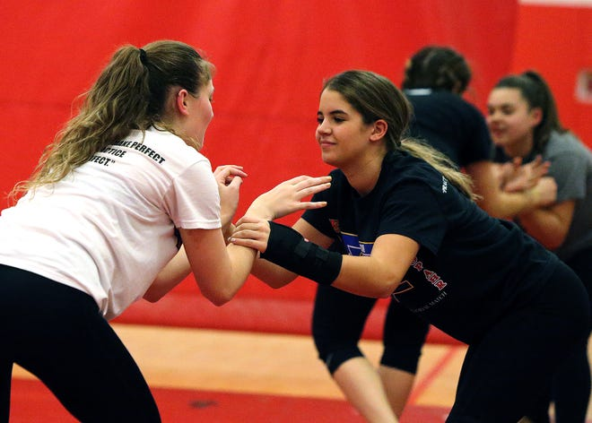 Gia Brito (right) and Kayla Natelli square off during Bishop Ahr High School's wrestling practice this week.