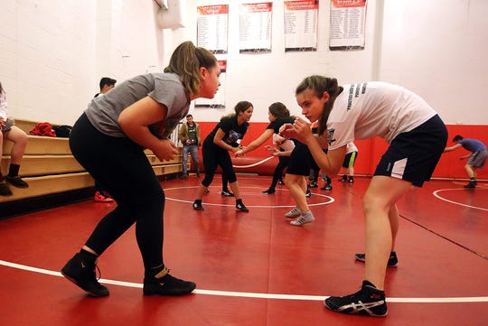 Olivia Hajdu-Nemeth (right) and Melissa Martinez drill during Bishop Ahr High School's wrestling practice this week.