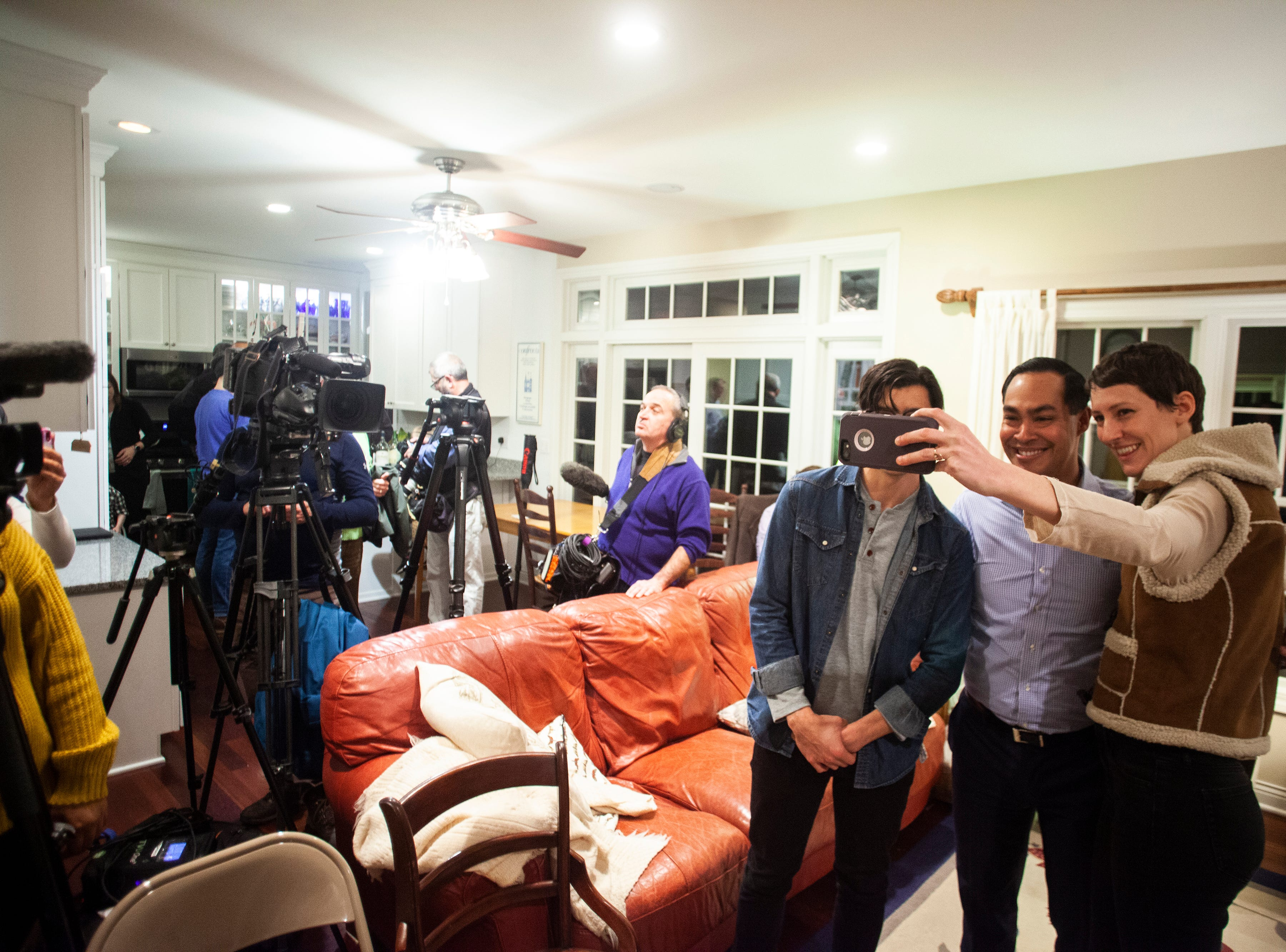 "Julián Castro poses for a photo with supporters at the Johnson County ""Potluck Insurgency"" on Monday, Jan. 7, 2019, at a home in North Liberty, Iowa."