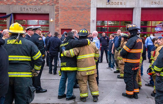 In this Sunday, Jan. 6, 2019, photo, firefighters embrace while gathered among fellow emergency responders after watching the procession for Lt. Eric Hosette pass Central Fire Station in Clinton, Iowa.