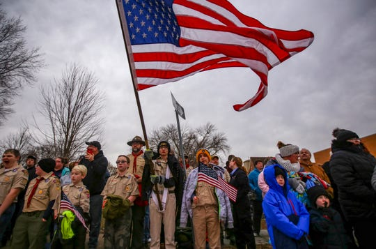 In this Sunday, Jan. 6, 2019, photo, Elijah Smith, 14, of Boy Scout Troop 642 of Clinton holds an American flag while awaiting the procession of Lt. Eric Hosette in Clinton, Iowa.