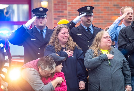 In this Sunday, Jan. 6, 2019, photo, Kelly Hosette, wife of fallen Clinton firefighter Lt. Eric Hosette, places her hand over her heart as the procession stops in front of Clinton's Central Fire Station in Clinton, Iowa.