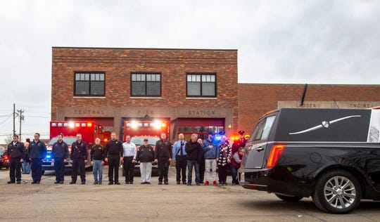 In this Sunday, Jan. 6, 2019, photo, the procession for fallen Clinton firefighter Lt. Eric Hosette passes by Central Fire Station in Clinton before arriving at the funeral home in Clinton, Iowa.