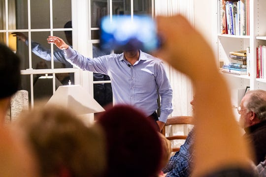 "A person takes a photo while Julián Castro speaks to supporters and local activists at the Johnson County ""Potluck Insurgency"" on Monday, Jan. 7, 2019, at a home in North Liberty, Iowa."