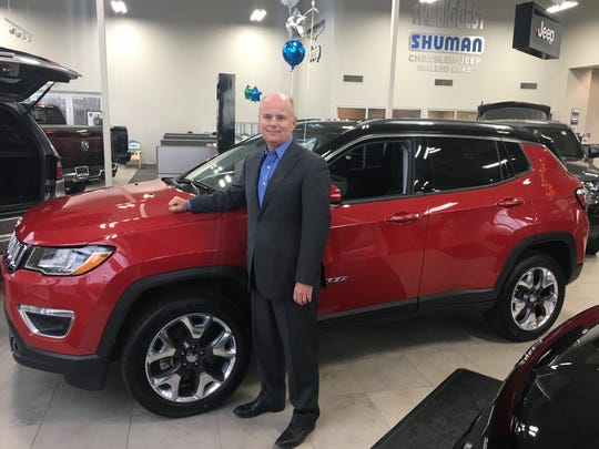 Dealer Bob Shuman of Shuman Chrysler Dodge Jeep Ram Walled Lake stands with the hot-selling 2019 Jeep Compass SUV.