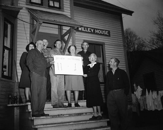 Voters of the tiny mountain hamlet of Hart's Location, N.H., show how they voted for Governor Thomas E. Dewey 11-1 as they stand outside the voting place on Nov. 2, 1948. Left to right; Mrs. Macomber, town clerk Douglas Macomber; Joseph Burke, Preston King, Mrs. George Morey and George Morey. The town, first in the country to report complete returns, voted at dawn.