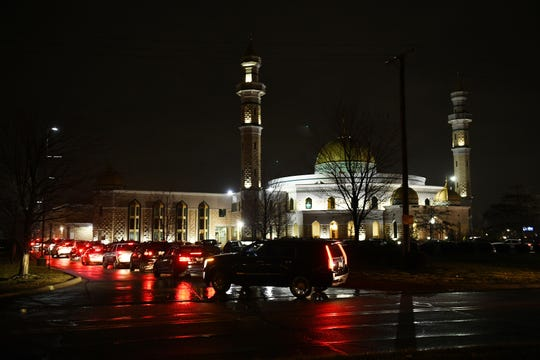 People arrive at the Islamic Center of America in Dearborn Monday night for the visitation for the Abbas family and five other services.