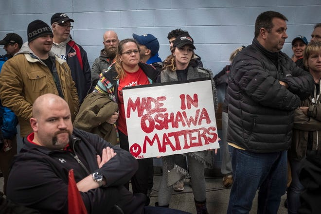 Laurie Nickel, center left, and her daughter Stephanie hold a sign during a UNIFOR union meeting between the workers of Oshawa's General Motors plant with Jerry Dias, president of UNIFOR, at the plant in Oshawa, Ontario, Monday, Nov. 26, 2018. General Motors will cut up to 14,000 workers in North America and put five plants up for possible closure as it abandons many of its car models and restructures to focus more on autonomous and electric vehicles, the automaker announced Monday. (Eduardo Lima/The Canadian Press via AP)