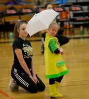 The Shining Stars Dance Team performs during halftime of the North Fond du Lac High School vs. St. Mary's Springs Academy girls basketball game on Jan. 4 at North Fond du Lac High School.  Sarah Strean helps Tia VanLoo with her performance.