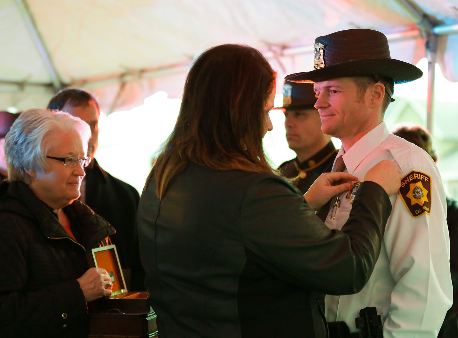 Sara Waldschmidt pins a sheriff's badge on her husband Ryan Waldschmidt Monday, January 7, 2019 outside the Fond du Lac Sheriff's Office after he is sworn in as the new sheriff of Fond du Lac County. Submitted by Roxanne Abler/USA TODAY NETWORK-Wisconsin
