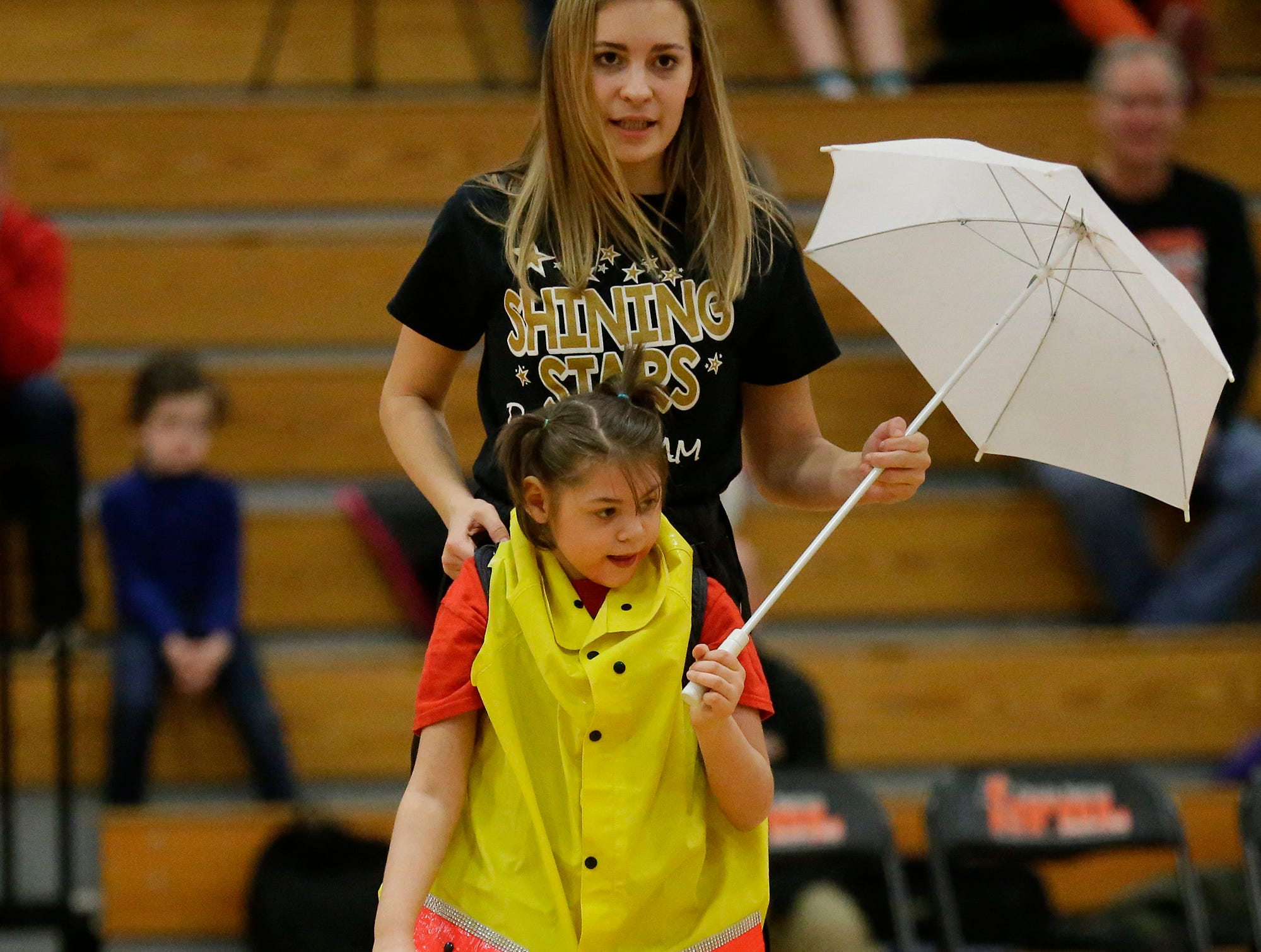 Gabrielle Feucht uses a specially made uniform to support Lyssa Brath as they perform with the Shining Stars Dance Team during halftime of the North Fond du Lac High School vs. St. Mary's Springs Academy girls basketball game Jan. 4 at North Fond du Lac High School.