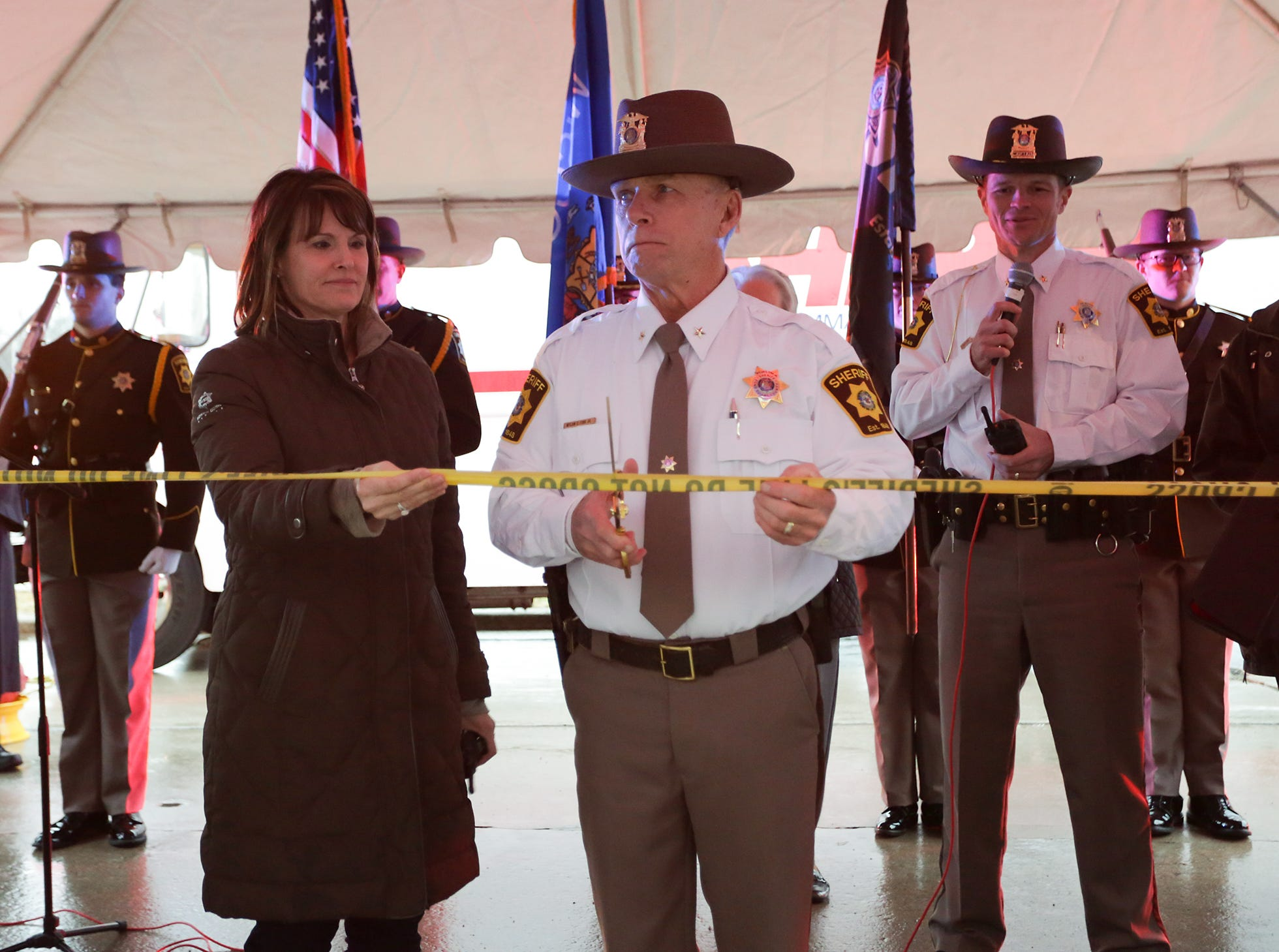 Recently retired Fond du Lac County Sheriff Mick Fink, standing next to his wife Mickie, cuts a ribbon of yellow sheriff's line tape to symbolize becoming a non elected citizen Monday, January 7, 2019 after doing the ramp walk on his last day as sheriff of Fond du Lac County. Fink retired from the position of Fond du Lac County Sheriff after serving for 12 years. Submitted by Roxanne Abler/USA TODAY NETWORK-Wisconsin