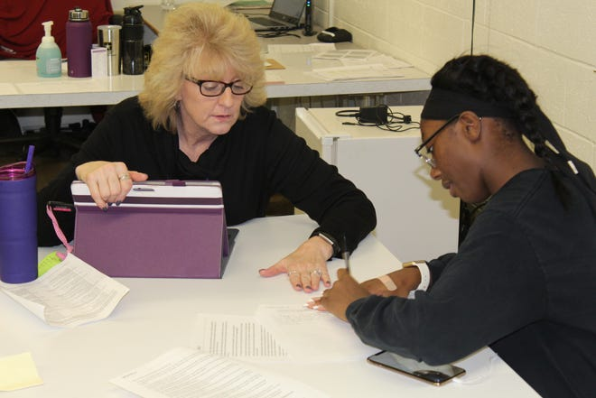 Kerri Hosang, an intervention specialist at Fremont Ross High School, works with sophomore Ashanti Elkins on her language arts argumentative essay Tuesday at the school's personalized learning center.