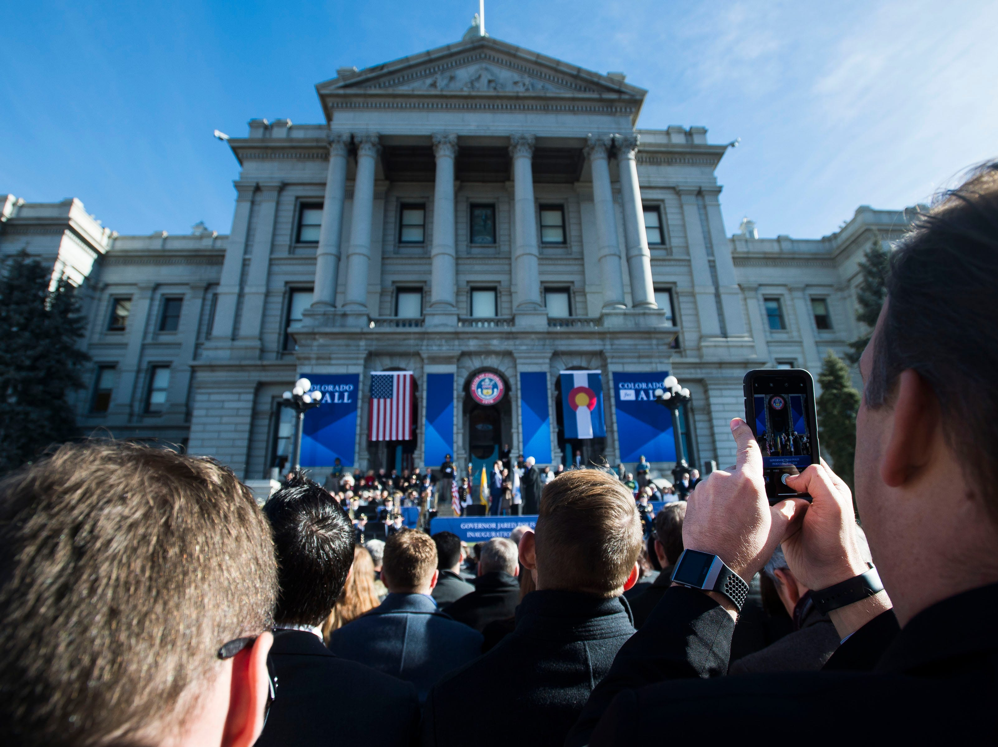 Erik Mitisek, right, takes a photo on his phone during the inauguration of Colorado State Governor Jared Polis on Tuesday, Jan. 8, 2019, in front of the Colorado State Capital building in Denver, Colo.