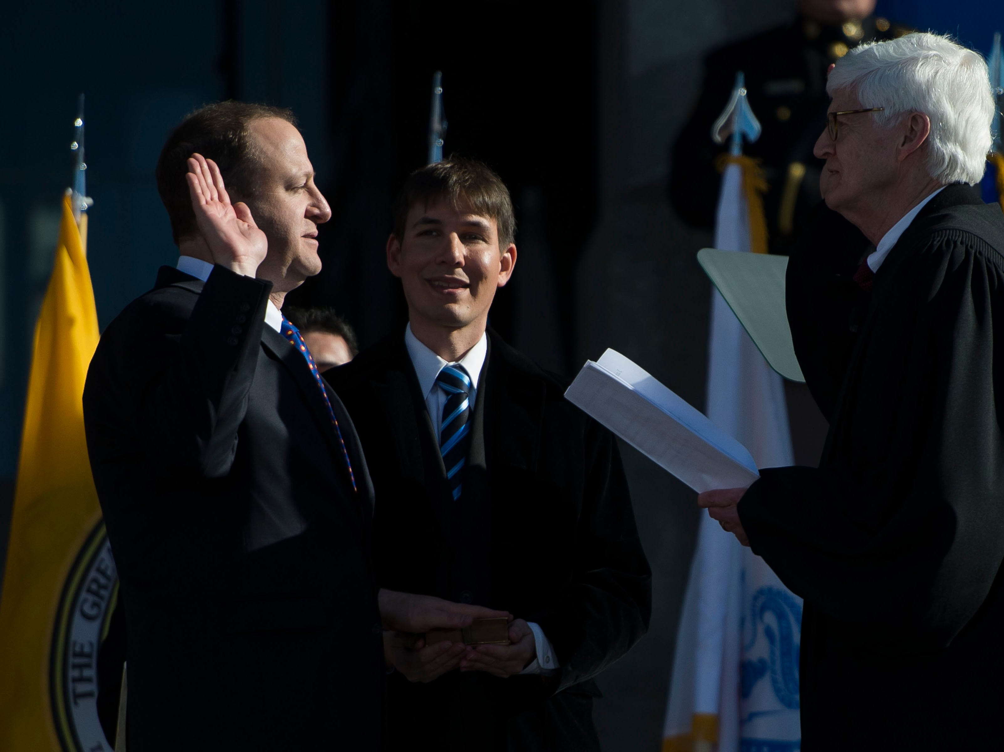 Governor Jared Polis, left, recites his oath of office, as directed by Chief Justice Nathan B. Coats, while Polis' partner Marlon Reis looks on during the inauguration of Colorado State Governor Jared Polis on Tuesday, Jan. 8, 2019, in front of the Colorado State Capital building in Denver, Colo.