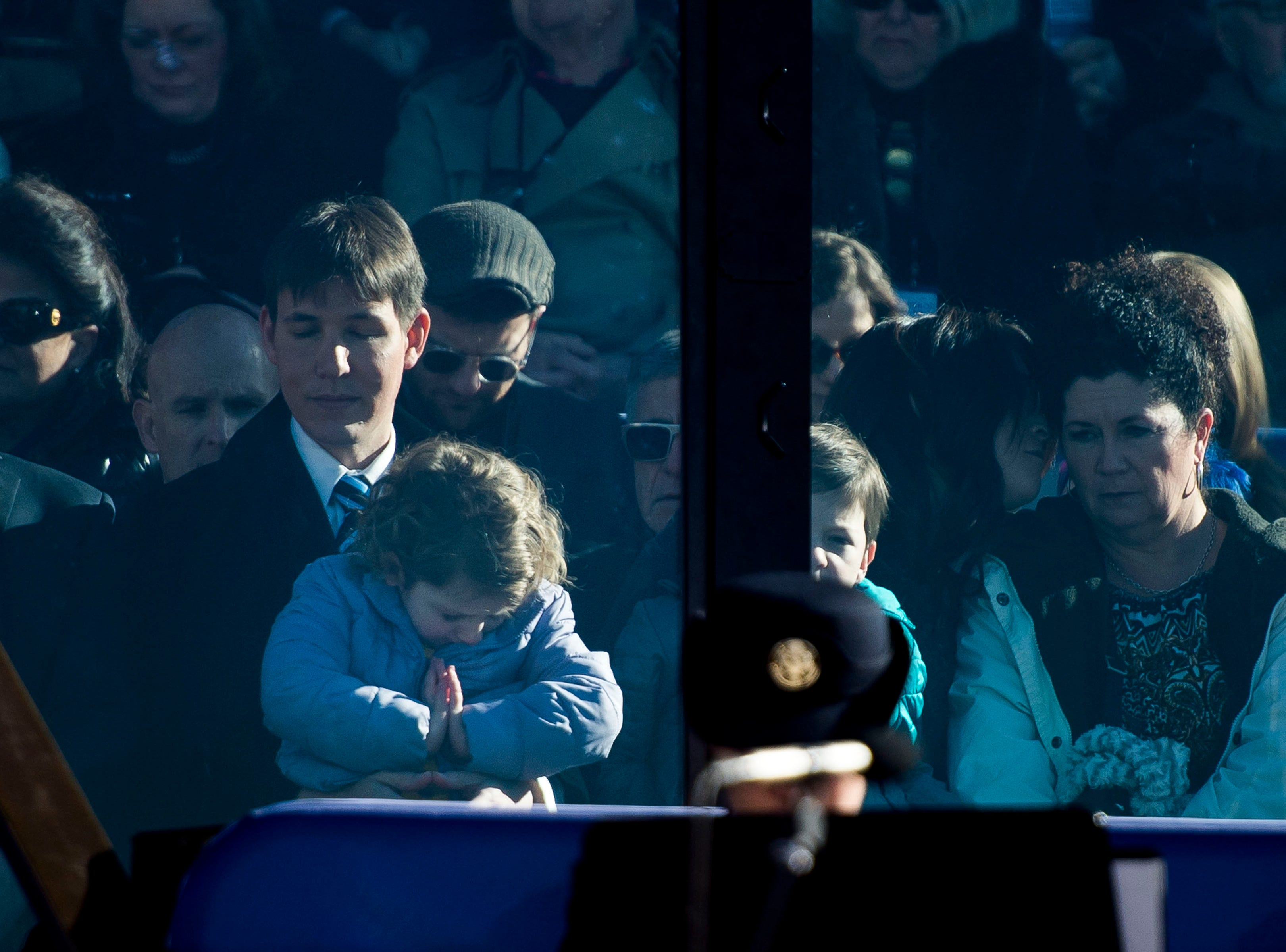 Governor Jared Polis and his partner Marlon Reis' daughter Cora Barucha Polis Reis, 4, prays while sitting on Marlon's lap at the beginning of the inauguration of Colorado State Governor Jared Polis on Tuesday, Jan. 8, 2019, in front of the Colorado State Capital building in Denver, Colo.