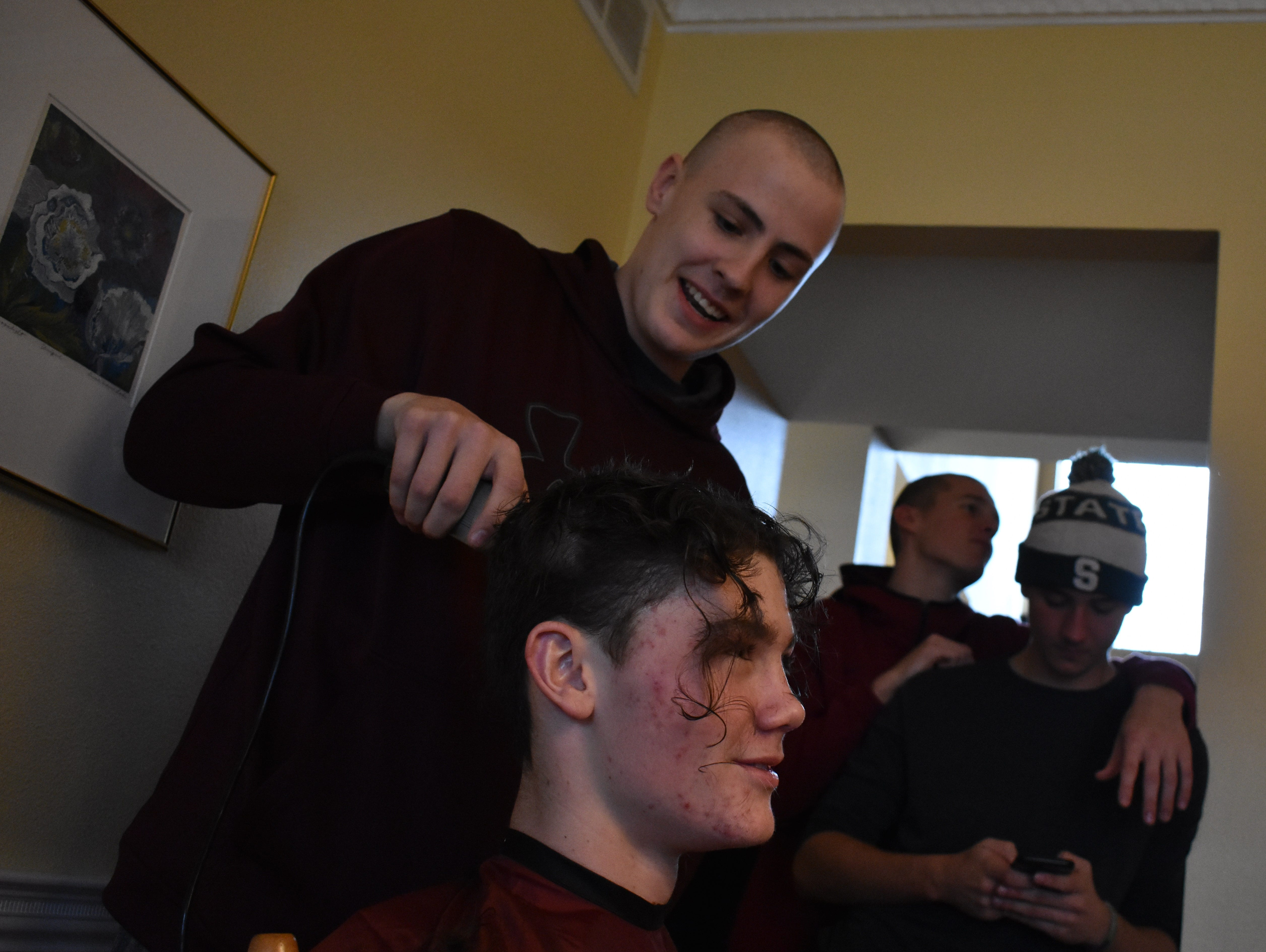 Rocky Mountain basketball player Carter Edgerley, who was recently diagnosed with cancer and shaved his head before losing his hair to chemotherapy treatments, shaves the head of teammate Dawson Otto on Dec. 31, 2018.