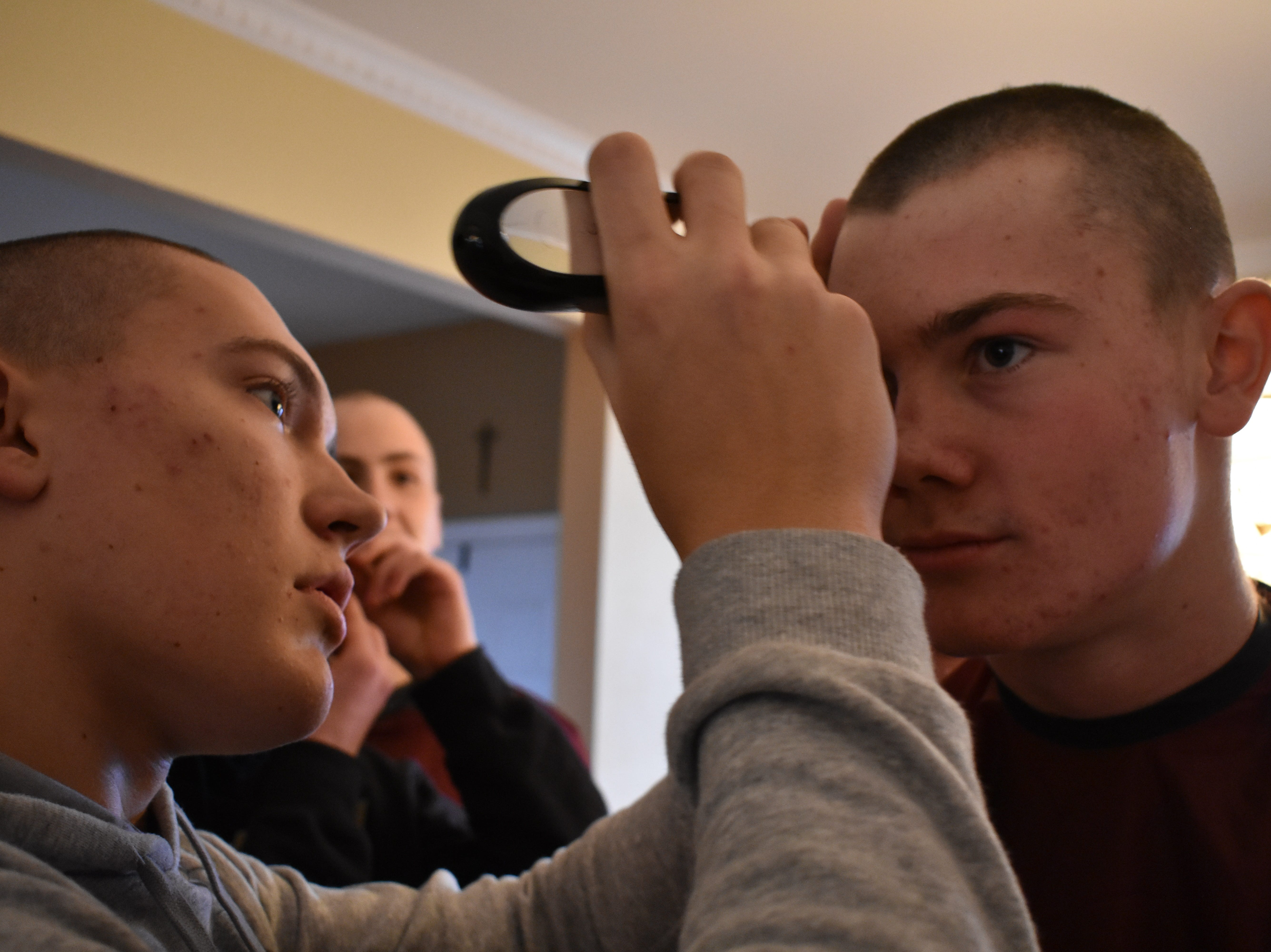 Rocky Mountain basketball player Peter Krohn shaves a mark into the eyebrow of teammate Dawson Otto Dec. 31, 2018, in support of teammate Carter Edgerely, who was recently diagnosed with bone cancer.