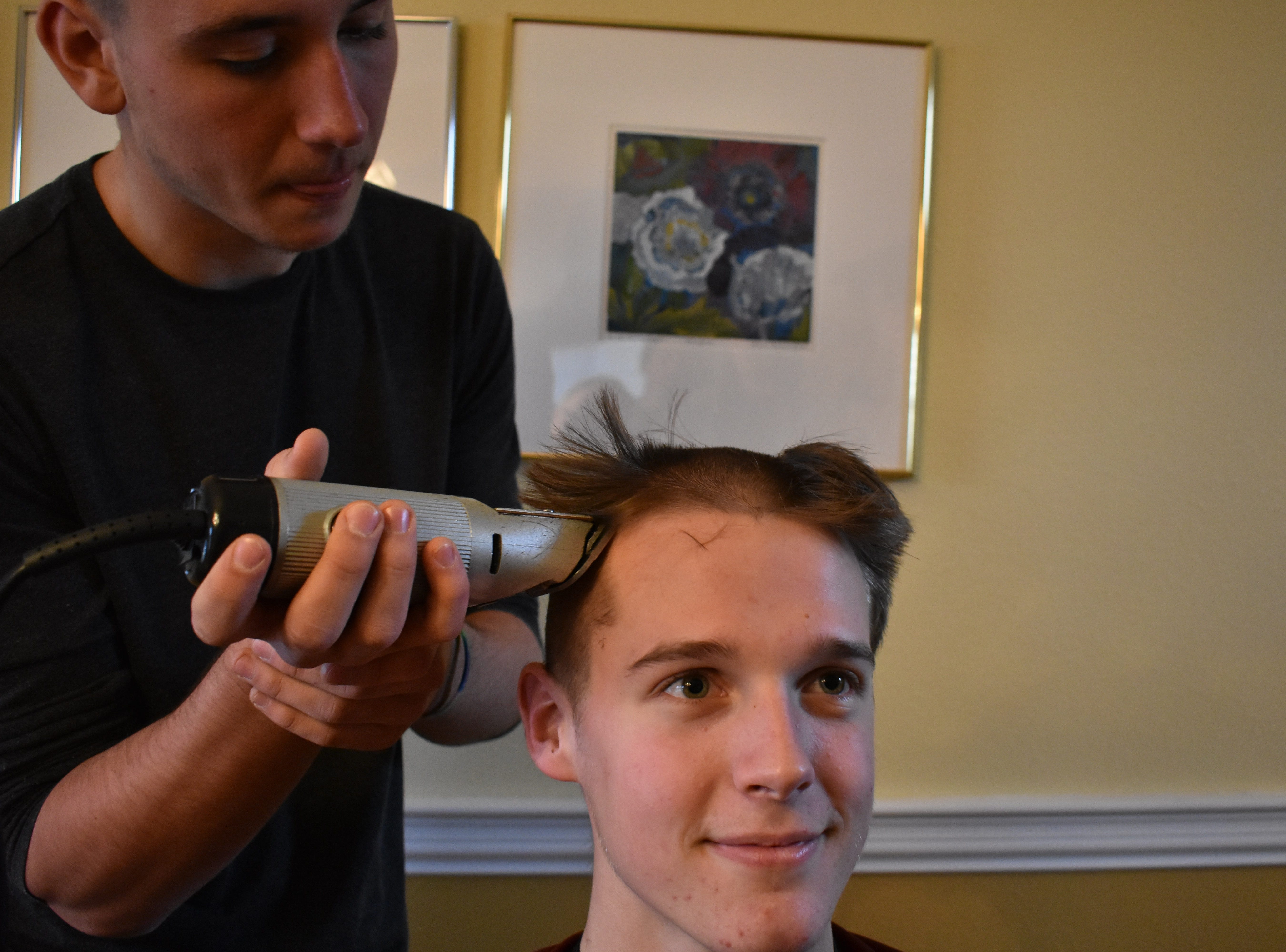 Joe Urynowicz shaves the head of Kenan Schuler Dec. 31, 2018, in support of teammate Carter Edgerely, who was recently diagnosed with bone cancer.