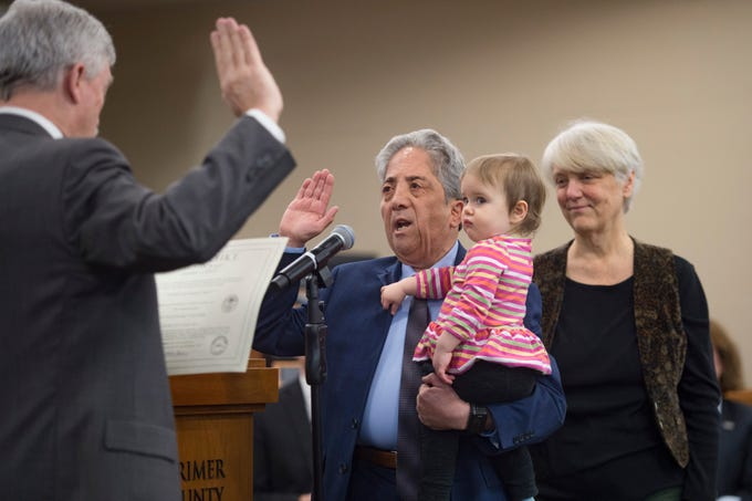 Larimer County Commissioner John Kefalas takes an oath of office holding his granddaughter Mila with his wife, Beth, at his side at the Larimer County Courthouse on Tuesday, January 8, 2019.