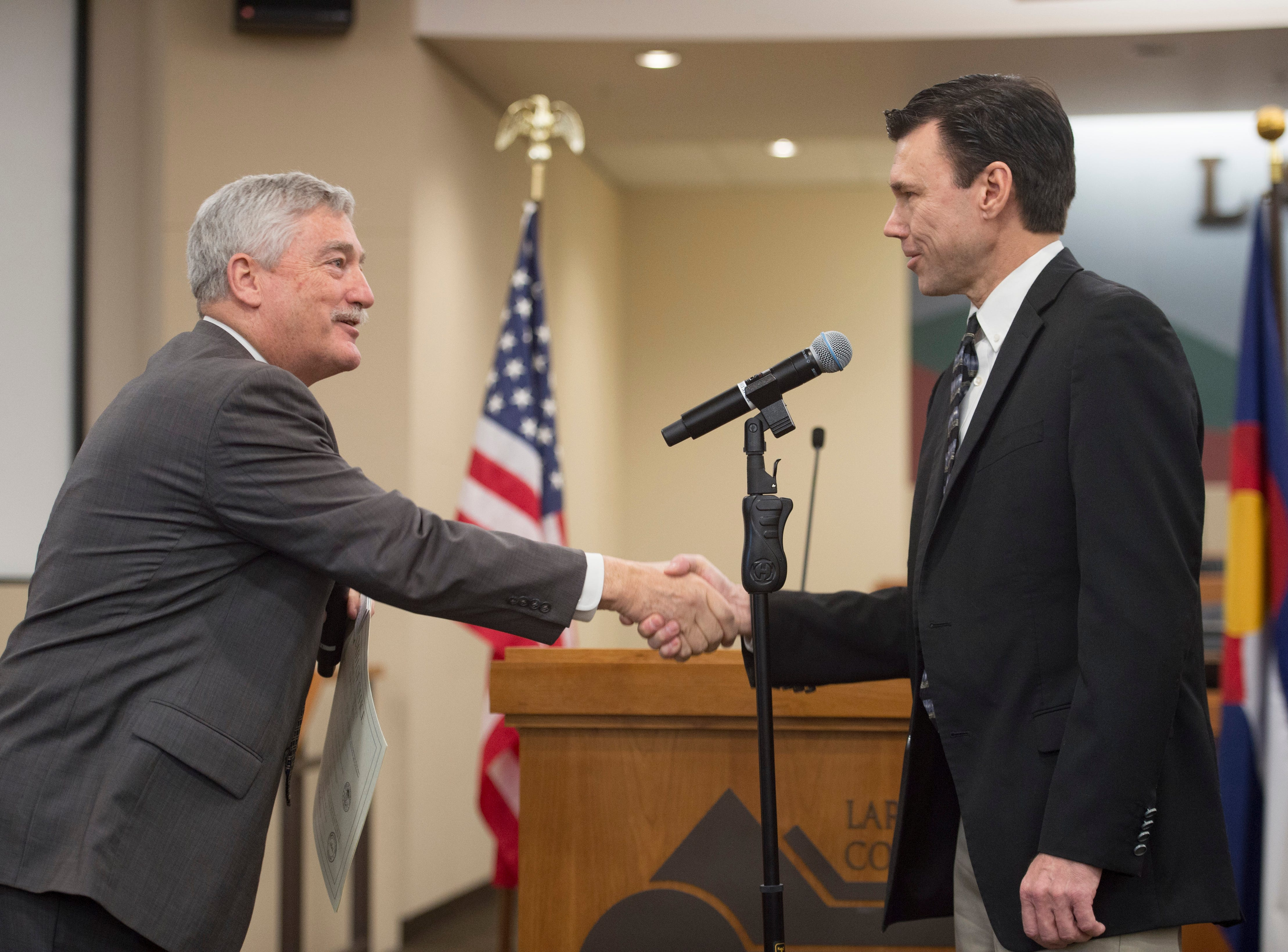 Judge Stephen Howard shakes hands with Larimer County Assessor Bob Overbeck after he is sworn in at the Larimer County Courthouse on Tuesday, January 8, 2019.