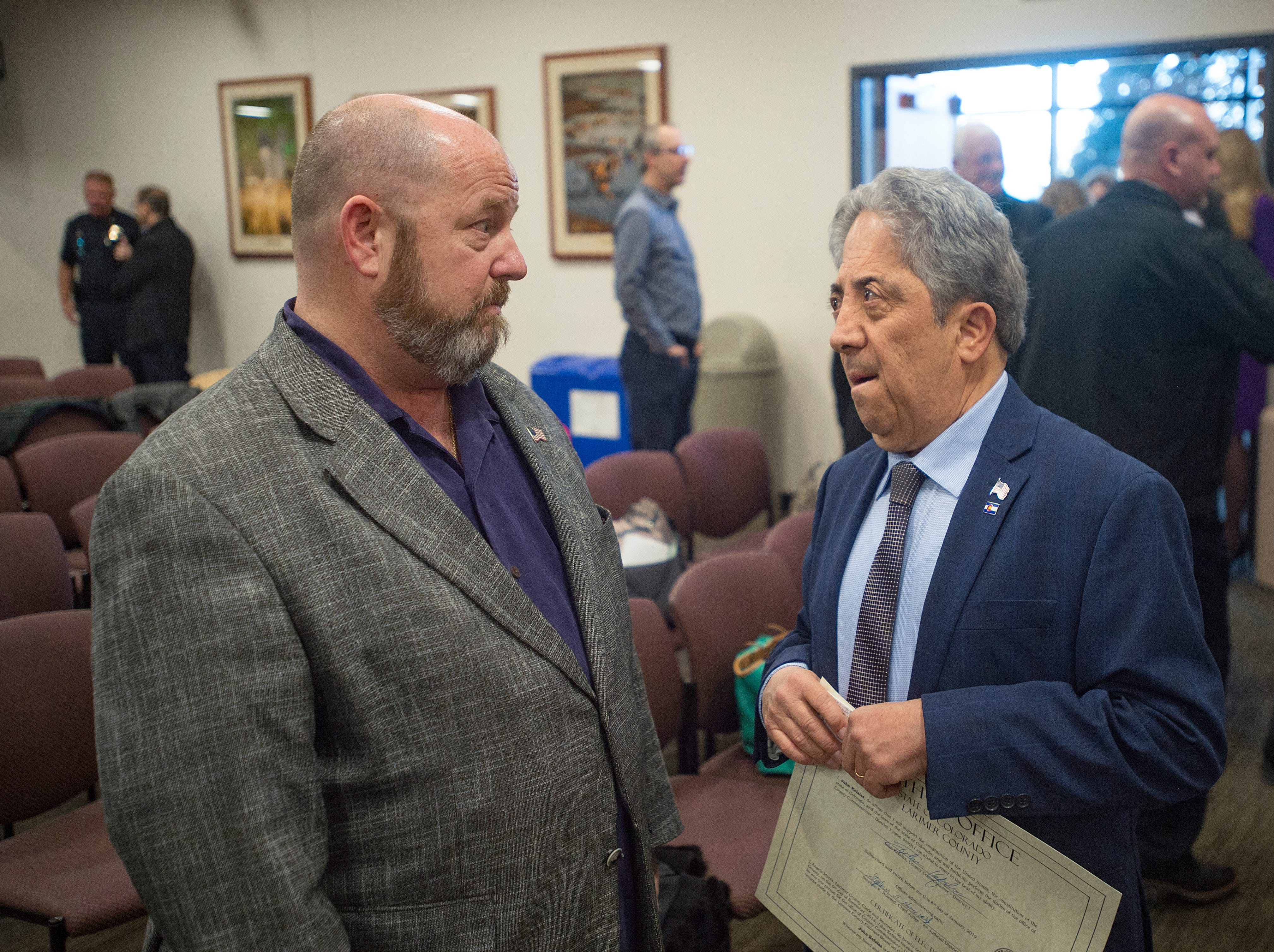 Outgoing commissioner Sean Dougherty talks with John Kefalas after he is sworn in as Larimer County Commissioner at the Larimer County Courthouse on Tuesday, January 8, 2019.