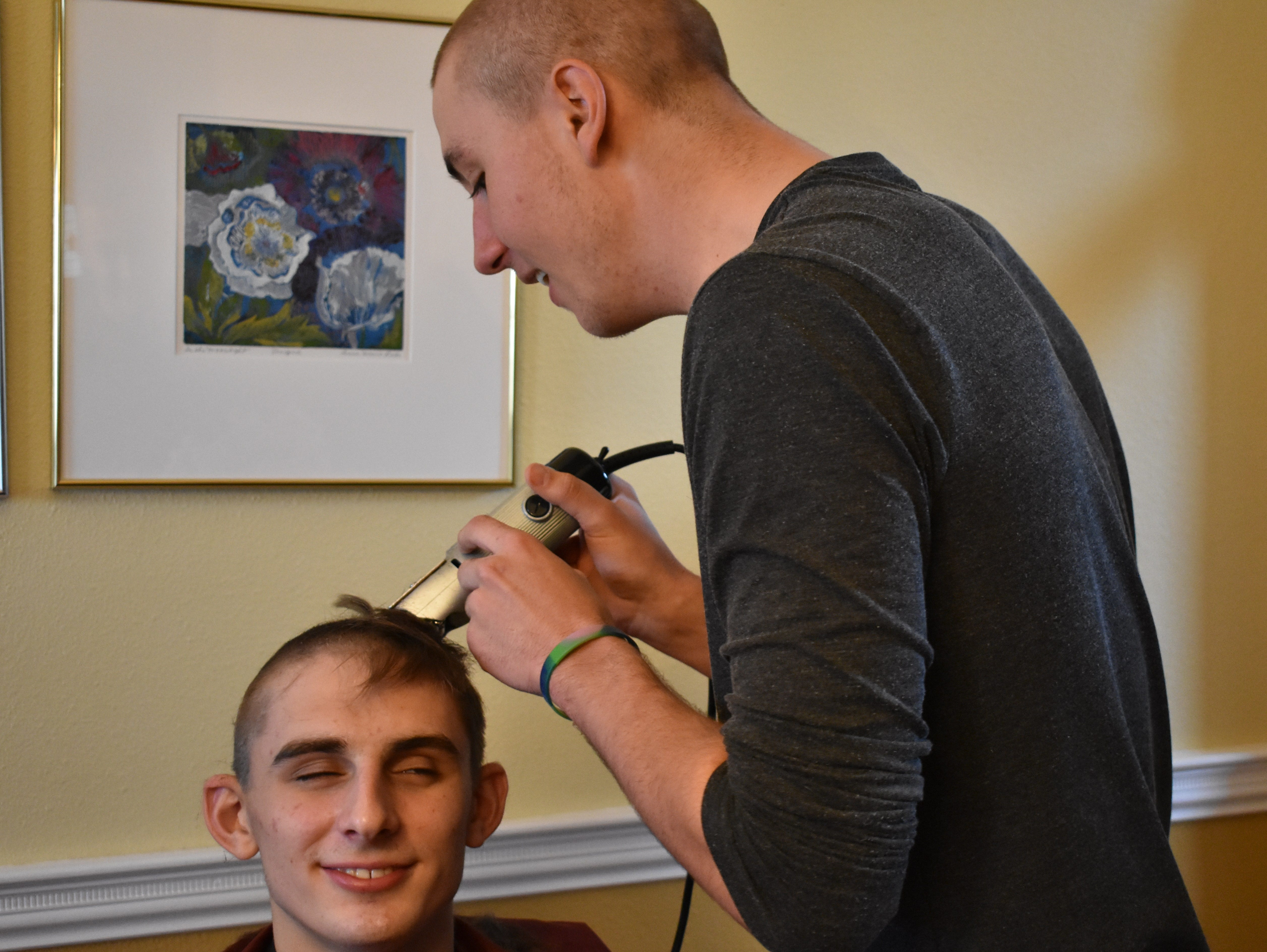 Tyler Fisher closes his eyes as Joe Urynowicz shaves his head Dec. 31, 2018, in support of teammate Carter Edgerely, who was recently diagnosed with bone cancer.