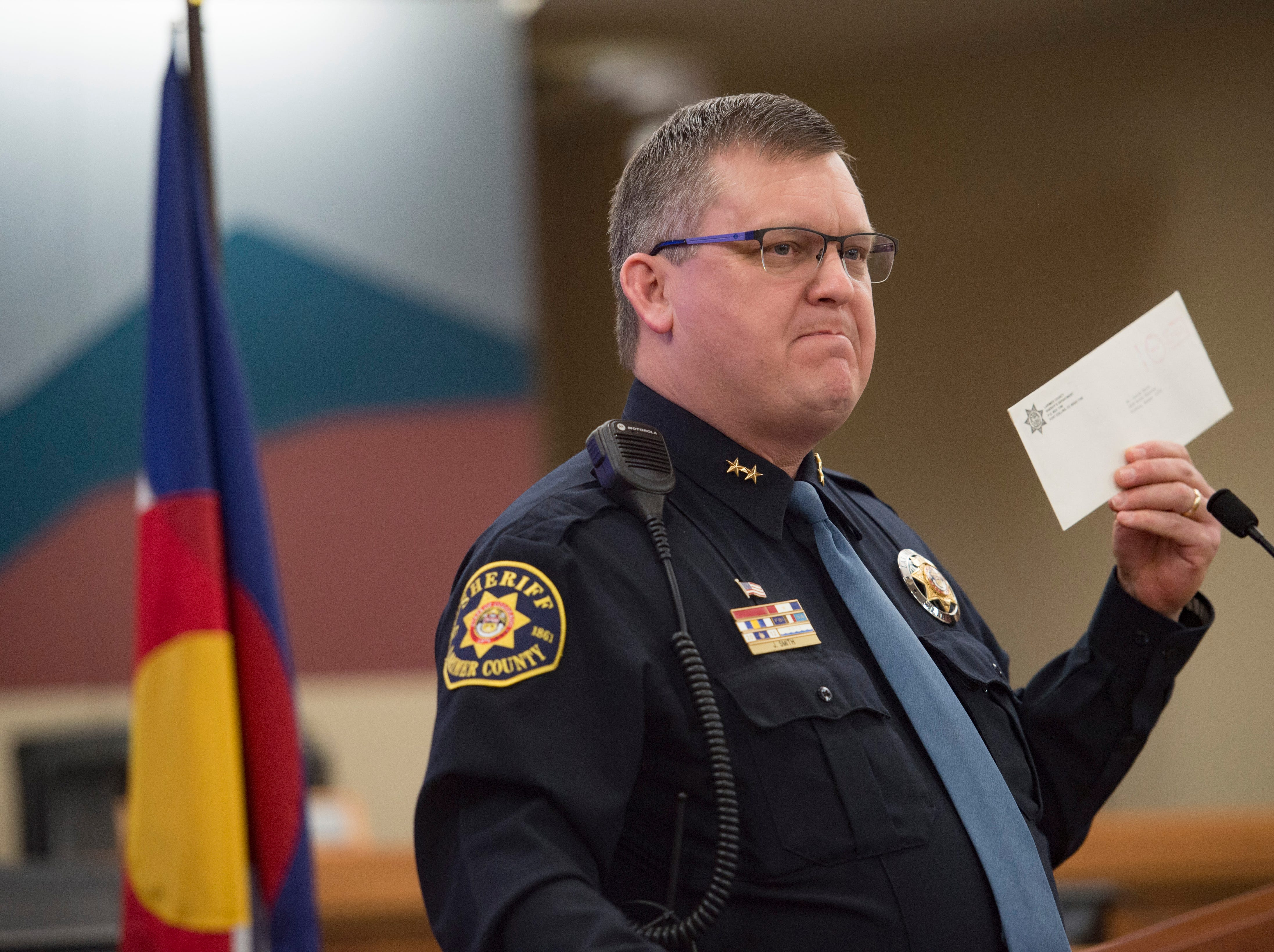 Larimer County Sheriff Justin Smith holds an envelope with his first contract he signed after joining the Sheriff's office in 1991 after he is sworn in for another term at the Larimer County Courthouse on Tuesday, January 8, 2019.