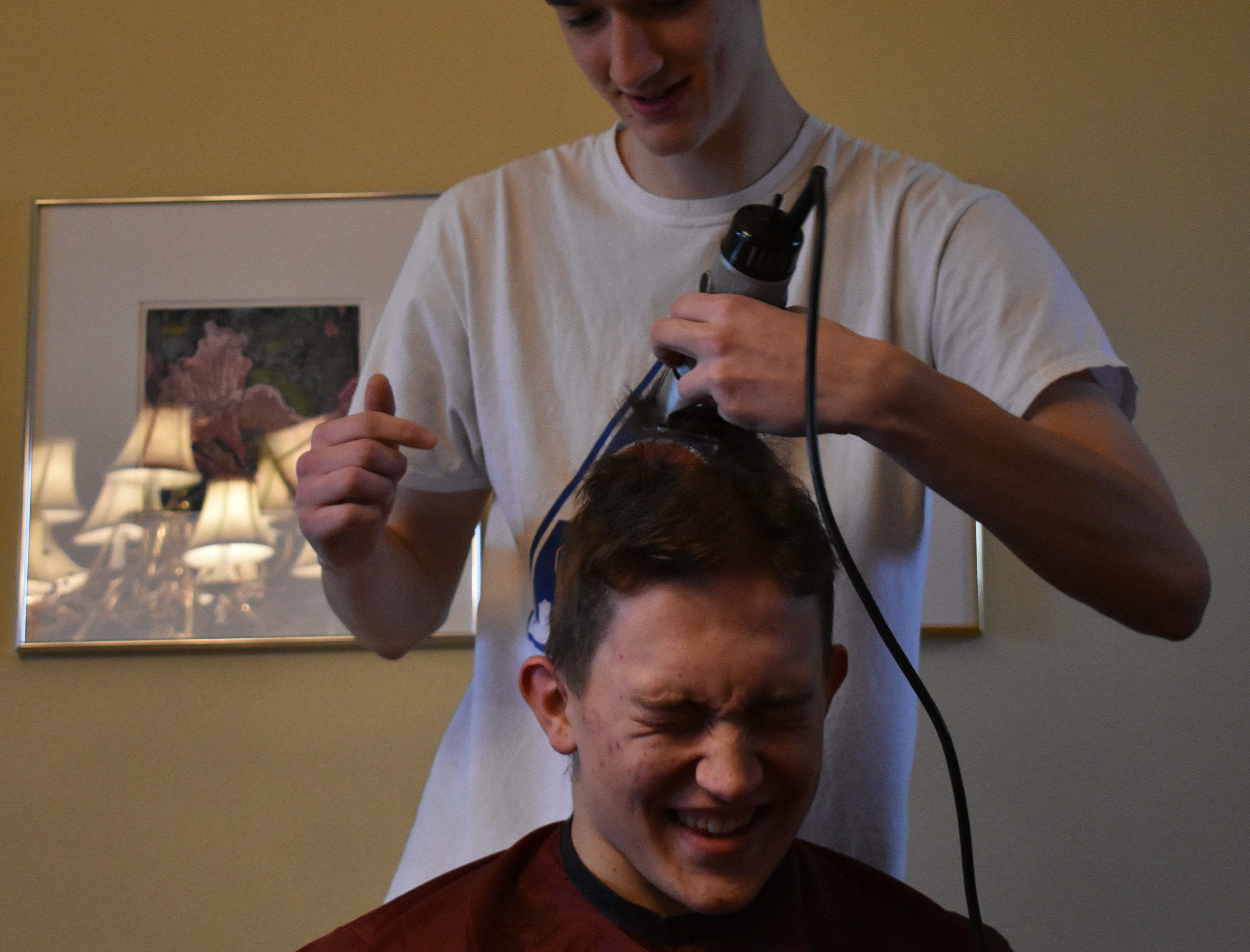 Peter Krohn reacts as Gilon Dierks shaves his head Dec. 31, 2018, in support of teammate Carter Edgerely, who was recently diagnosed with bone cancer.