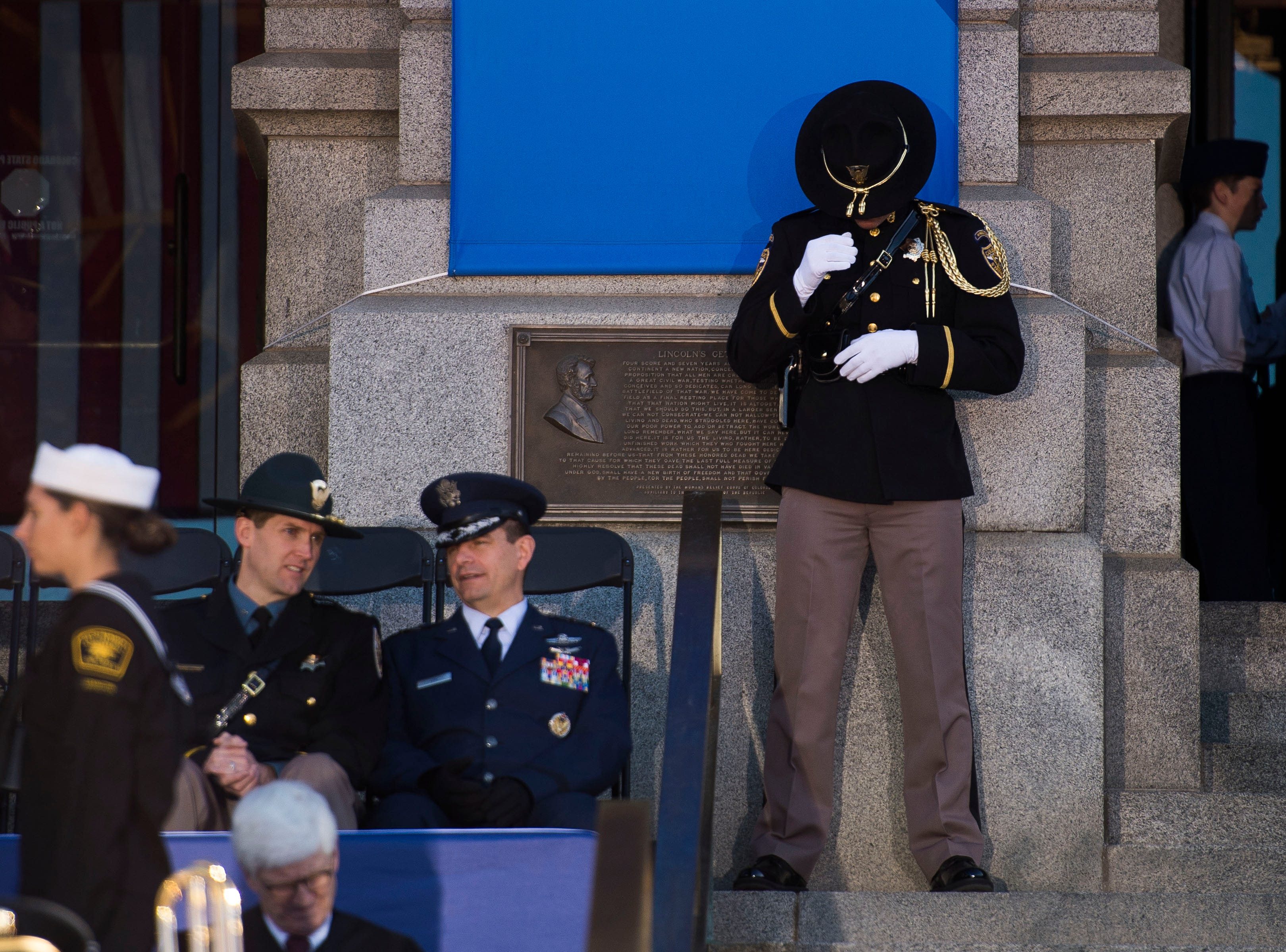 A Colorado State patrolman straitens his hat during the inauguration of Colorado State Governor Jared Polis on Tuesday, Jan. 8, 2019, in front of the Colorado State Capital building in Denver, Colo.