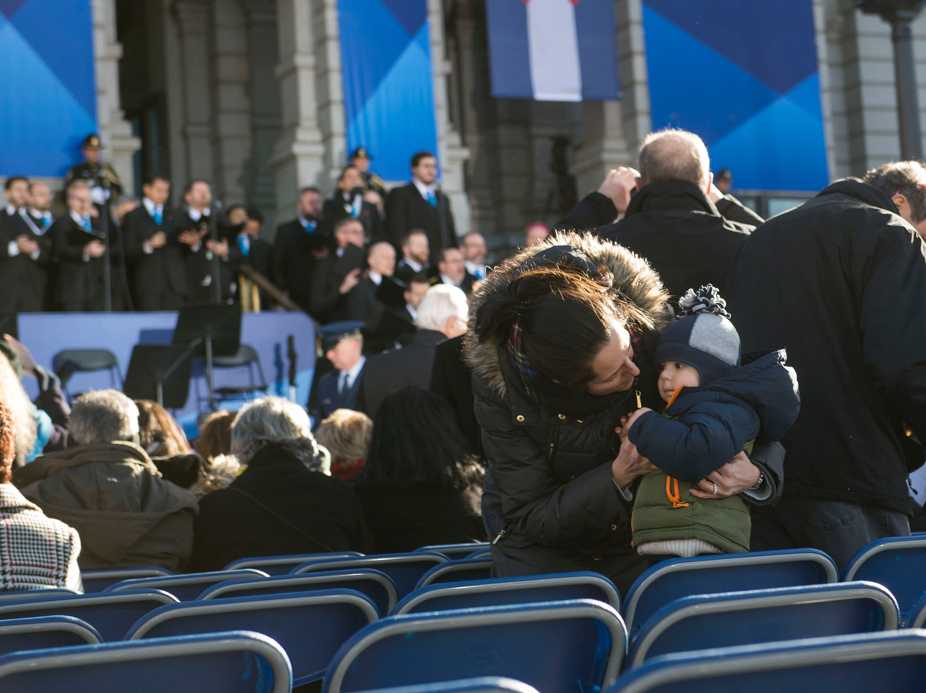 Michelle Weidler gives her one-year-old son Zachary a kiss while audience members find their seats before the inauguration of Colorado State Governor Jared Polis on Tuesday, Jan. 8, 2019, in front of the Colorado State Capital building in Denver, Colo.