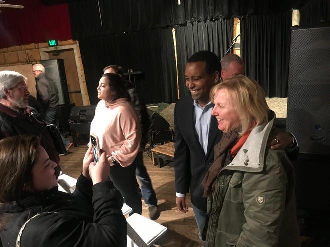 U.S. Rep. Joe Neguse, left, poses with a constituent after a Fort Collins town hall Monday night.