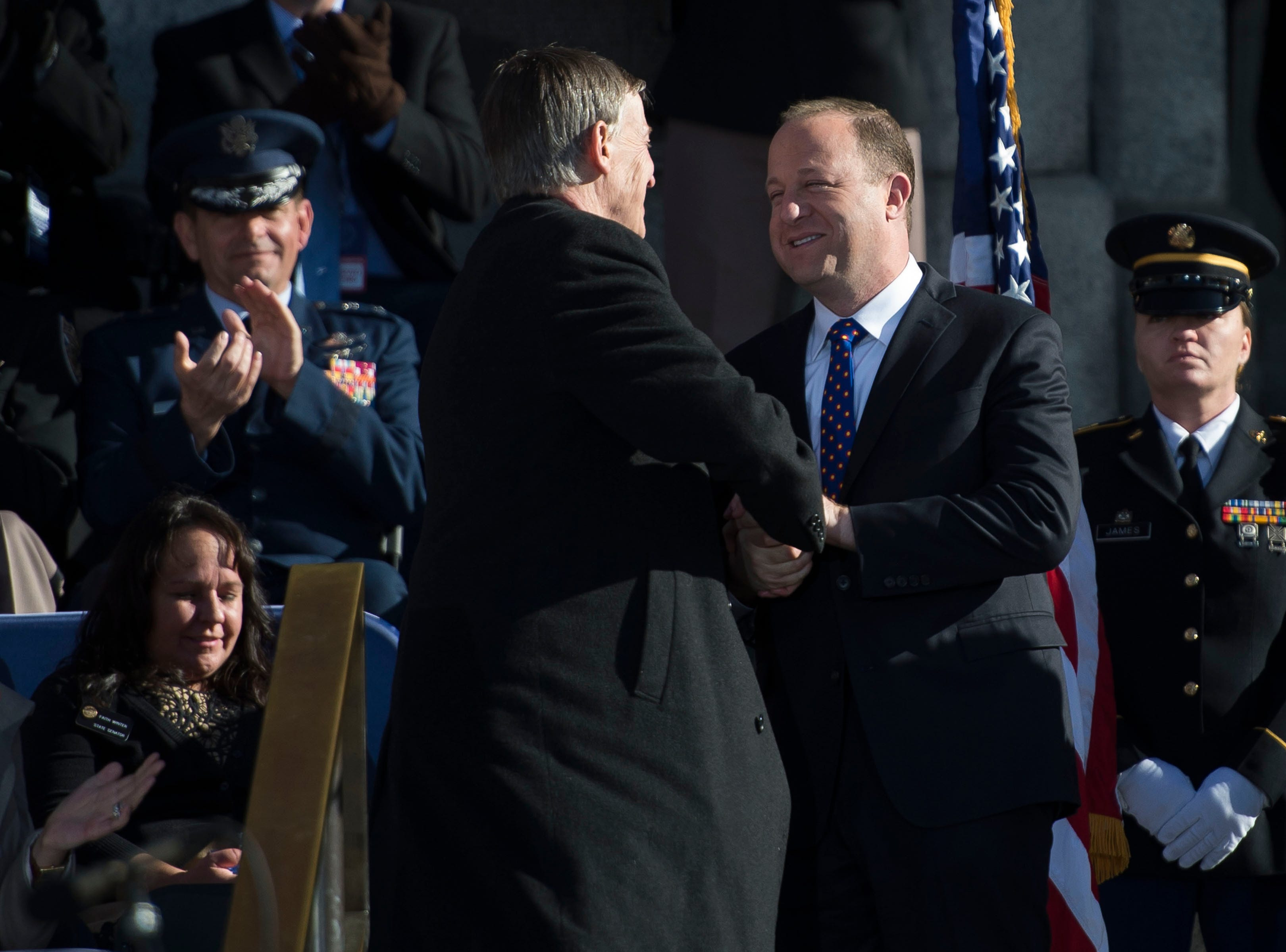 Governor Jared Polis greets outgoing Governor John Hickenlooper before giving his inaugural address on Tuesday, Jan. 8, 2019, in front of the Colorado State Capital building in Denver, Colo.