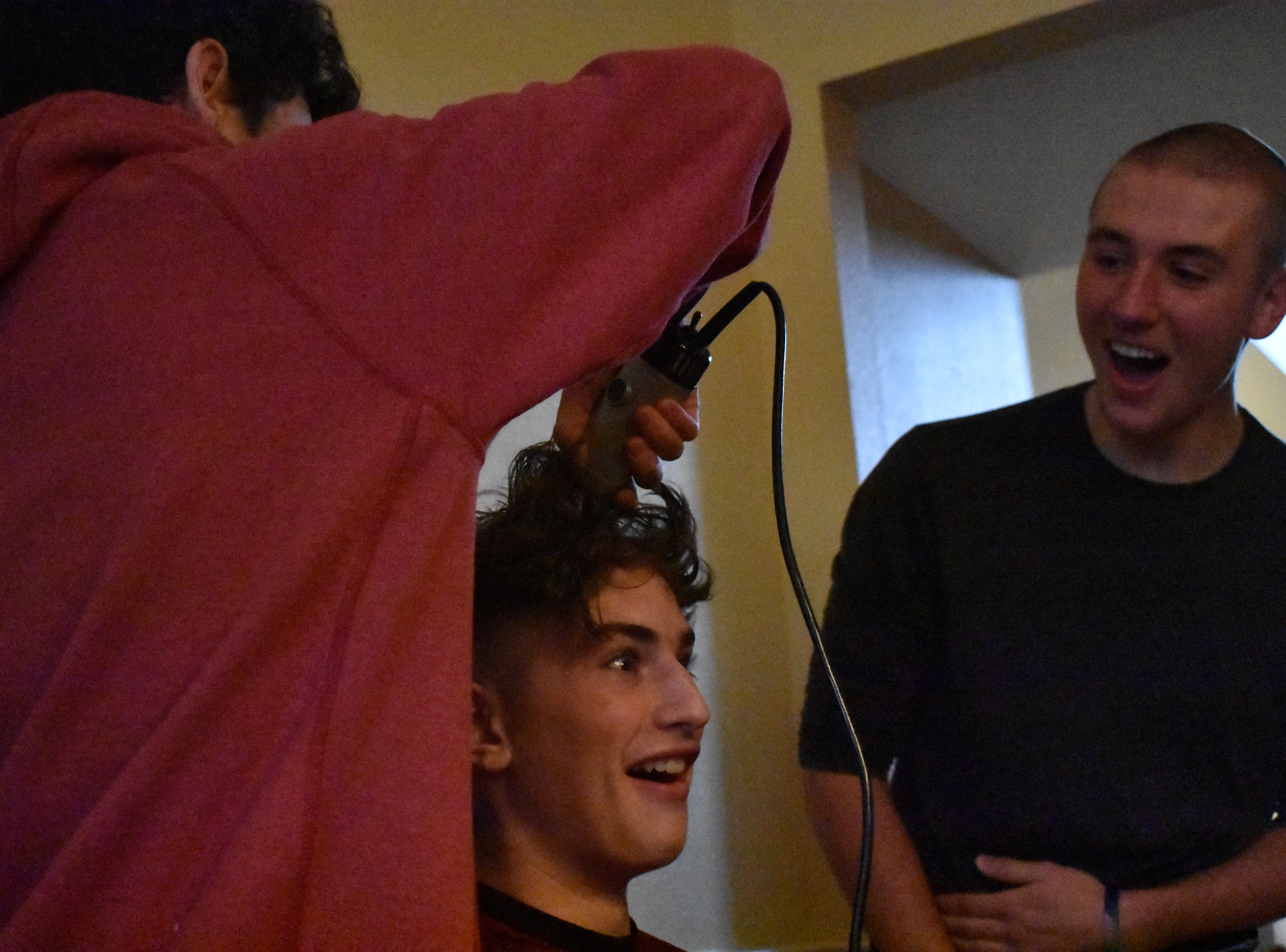 Leo Von Bargen reacts to Joseph Naddy shaving his head while Joe Urynowicz looks on during the Rocky Mountain basketball team's head shaving on Dec. 31, 2018, in support of teammate Carter Edgerely, who was recently diagnosed with bone cancer.