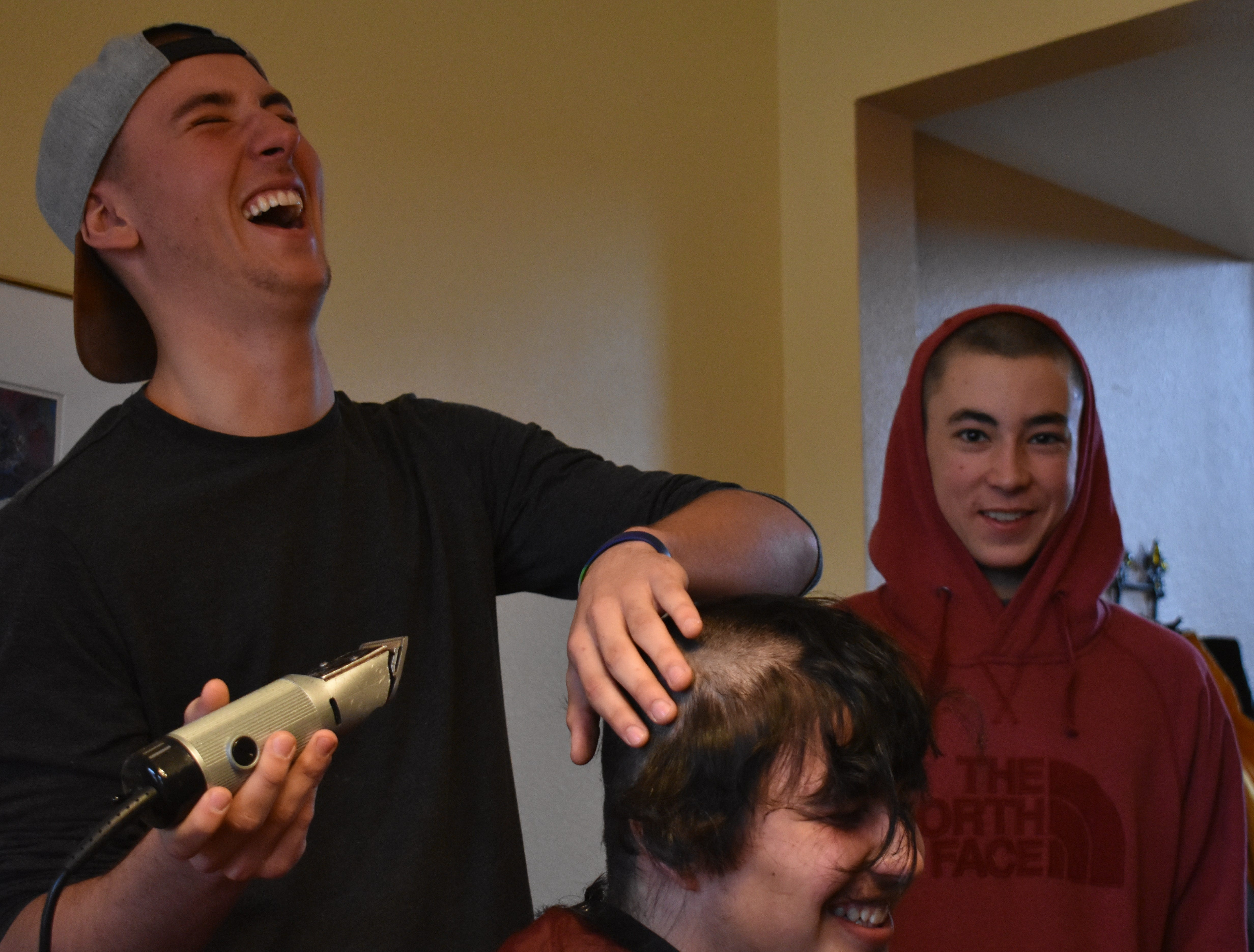Rocky Mountain basketball player Joe Urynowicz laughs while shaving the head of teammate Jaden Lucero Dec. 31, 2018, in support of teammate Carter Edgerely, who was recently diagnosed with bone cancer.