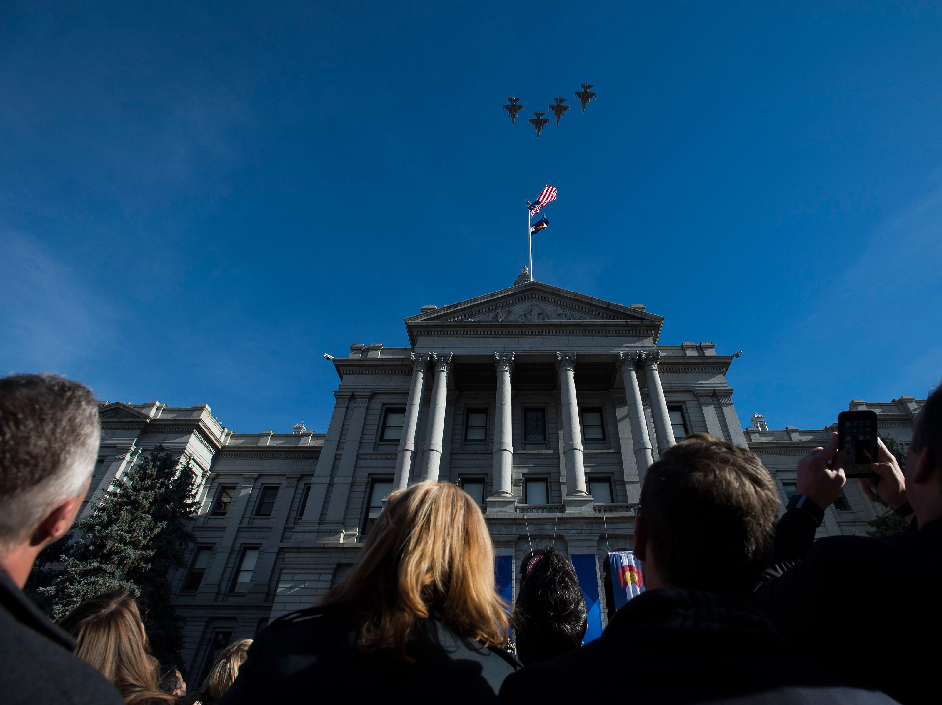 Military jets fly overhead at the conclusion of the inauguration of Colorado State Governor Jared Polis on Tuesday, Jan. 8, 2019, in front of the Colorado State Capital building in Denver, Colo.
