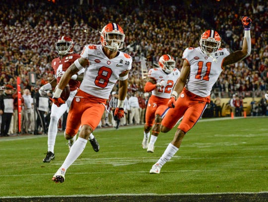 Clemson defensive back A.J. Terrell (8) returns an interception near teammate safety Isaiah Simmons (11) and Alabama defensive back Saivion Smith (4) during the first quarter of the College Football Championship at Levi's Stadium in Santa Clara, California Monday, January 7, 2019.