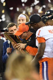 Clemson head coach Dabo Swinney holds up the National Championship trophy after the Tigers defeated Alabama.